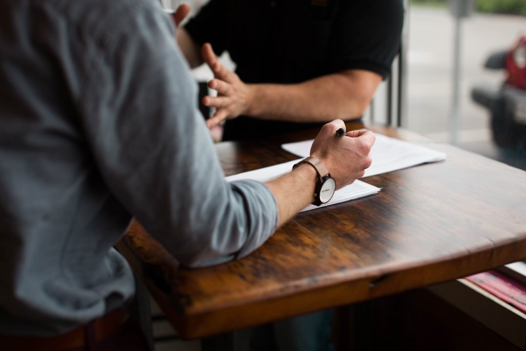 close up of hands at a table with paperwork